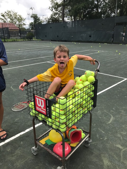 Child in tennis ball cart